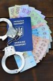 Une photographie d'un passeport étranger ukrainien, d'un argent ukrainien et de menottes de police Concept d'earnin illégal photographie stock libre de droits