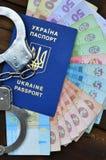 Une photographie d'un passeport étranger ukrainien, d'un argent ukrainien et de menottes de police Le concept d'arrêter image libre de droits