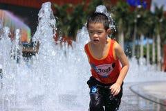 Une pièce asiatique de garçon par la fontaine d'eau Images stock