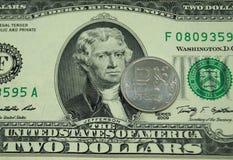 Une pièce dans un rouble se trouve sur un billet de deux dollars Images stock