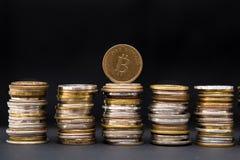Une pièce de monnaie artificielle de bitcoin sur la pile de pièces de monnaie mélangées, sur le fond foncé avec l'espace des text photo stock