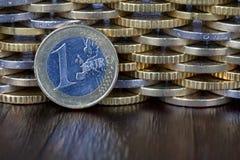 Une pièce de monnaie d'un euro devant un mur des pièces de monnaie plus euro de diff Images stock