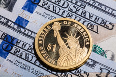 Une pièce du dollar - la statue de la liberté - sur cent billets d'un dollar Photographie stock