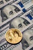 Une pièce du dollar - la statue de la liberté - sur cent billets d'un dollar Image stock