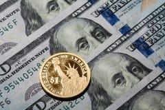 Une pièce du dollar - la statue de la liberté - sur cent billets d'un dollar Photographie stock libre de droits