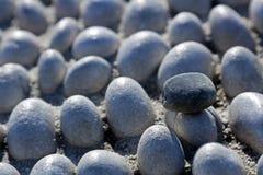 Une pierre noire sur un tapis en pierre blanc Photographie stock libre de droits