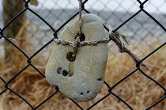 Une pierre portée par mer avec deux trous dans elle est astucieusement attachée à une barrière photos libres de droits