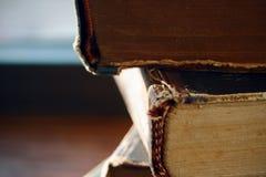 Une pile d'épine menteuse de vieux livres bousillés de cru en avant images stock