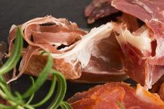 Une pile d'embutido, de jamon, de chorizo et de fin de support espagnols différents de lomo Image stock