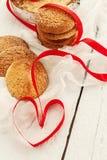 Une pile de biscuits ronds et un ruban rouge sous forme de hea Photographie stock libre de droits