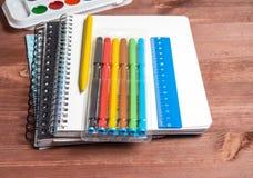 Une pile de carnets, de stylos, de crayons et d'aquarelles sur un fond en bois Photos stock
