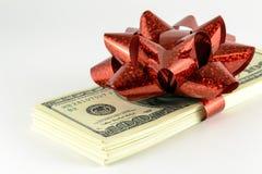 Une pile de dollars et un cadeau rouge cintrent Photos libres de droits