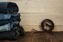 Une pile de jeans sur un fond en bois et une ceinture Photo libre de droits