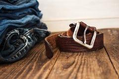 Une pile de jeans sur un fond en bois et une ceinture Photographie stock libre de droits