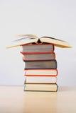 Une pile de livres épais colorés sur une table Photos stock