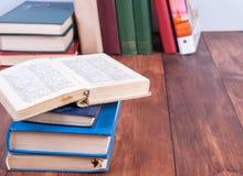 Une pile de livres avec un livre ouvert se trouvant sur le dessus Image stock