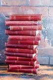 Une pile de livres avec une couverture dure rouge foncé une une autre sur une table en bois dans la perspective de mur de briques Photographie stock