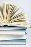 Une pile de livres bleus sur le fond bleu-clair Image stock