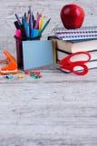 Une pile de livres, de papeterie, d'une pomme et de feuilles sur un fond en bois Le concept de l'éducation Photographie stock