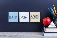 Une pile de livres, papeterie et une pomme rouge, sur un fond foncé avec l'inscription de nouveau à l'école Image libre de droits