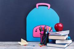 Une pile de livres, papeterie et une pomme, sur un fond avec une image d'un sac à dos de papier Le concept de l'éducation Photographie stock