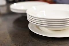 Une pile de plats blancs sur une table de cuisine foncée Photographie stock