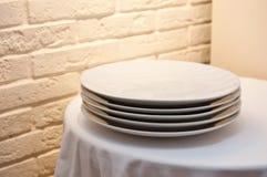 Une pile de plats de dîner blancs sur une table sur un fond de mur de briques image stock