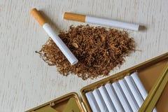 Une pile de tabac naturel sur une table en bois blanche, un dispositif pour la production manuelle des cigarettes et des cigarett image libre de droits