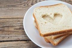 Une pile de tranches de pain blanc d'un plat sur une table en bois Photos stock