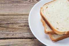 Une pile de tranches de pain blanc d'un plat sur une table en bois Photos libres de droits