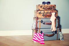 Une pile de vieux voyage de vintage met en sac dans la chambre bloquée avec des garmen Photographie stock