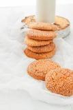 Une pile des biscuits sablés ronds et d'une bouteille de lait, sur W Photographie stock