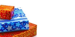 Une pile des cadeaux colorés de Noël d'isolement sur le blanc Photos libres de droits