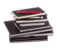 Une pile des carnets d'affaires et du crayon rouge Photos stock