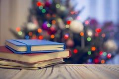 Une pile des carnets sur une table en bois contre l'arbre de Noël décoré Photographie stock libre de droits