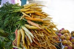 Une pile des carottes multicolores avec des dessus dessus avec les pommes de terre blanches et rouges brouillées à l'arrière-plan images libres de droits