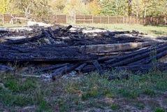 Une pile des cendres et des planches roussies sur le site d'un feu de maison Photos libres de droits