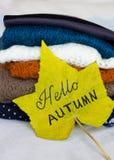 Une pile des chandails chauds et d'une feuille d'érable jaune Photo stock