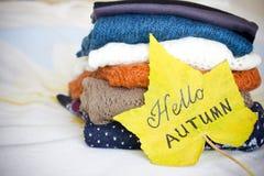 Une pile des chandails chauds et d'une feuille d'érable jaune Image stock
