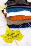 Une pile des chandails chauds et d'une feuille d'érable jaune Images stock