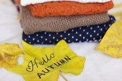 Une pile des chandails chauds et d'une feuille d'érable jaune Photographie stock
