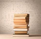 Une pile des livres avec des formules de maths écrites dans le style de griffonnage Photographie stock