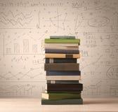 Une pile des livres avec des formules de maths écrites dans le style de griffonnage Photo stock