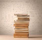 Une pile des livres avec des formules de maths écrites dans le style de griffonnage Photos stock