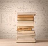 Une pile des livres avec des formules de maths écrites dans le style de griffonnage Image stock