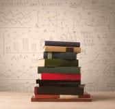 Une pile des livres avec des formules de maths écrites dans le style de griffonnage Photographie stock libre de droits