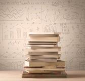 Une pile des livres avec des formules de maths écrites dans le style de griffonnage Images libres de droits