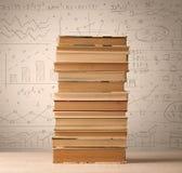 Une pile des livres avec des formules de maths écrites dans le style de griffonnage Images stock