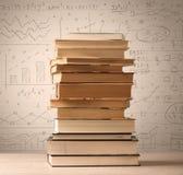Une pile des livres avec des formules de maths écrites dans le style de griffonnage Image libre de droits