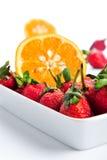 Une pile des oranges avec des fraises Image stock
